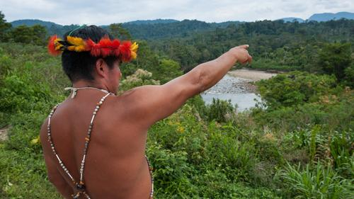 Standing above the Numbkataime River, Shuar leader Patricio Wampash points to nearby peaks and a critical watershed that is slated for mining.
